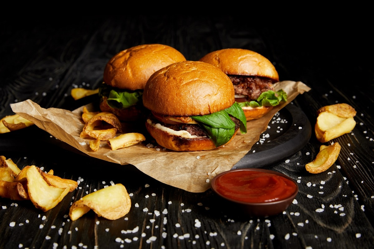 Tasty hamburgers and french fries with ketchup on wooden board